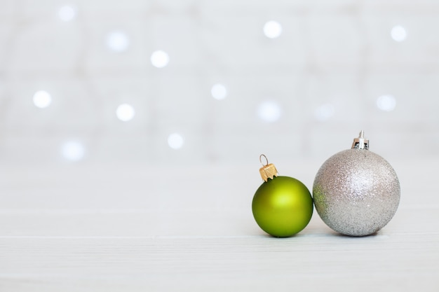 Wooden background with green balls and gifts.