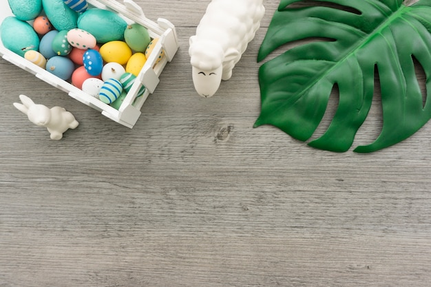 Wooden background with green leaf and easter objects