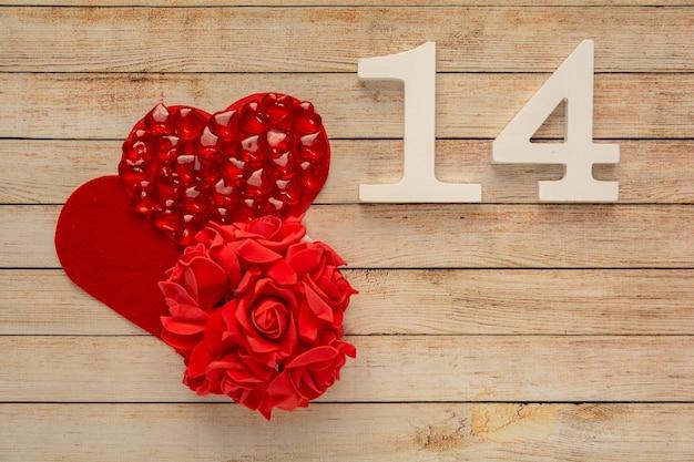 2月14日付の木製の背景にハート、花、木製の番号。バレンタインデーのコンセプト。