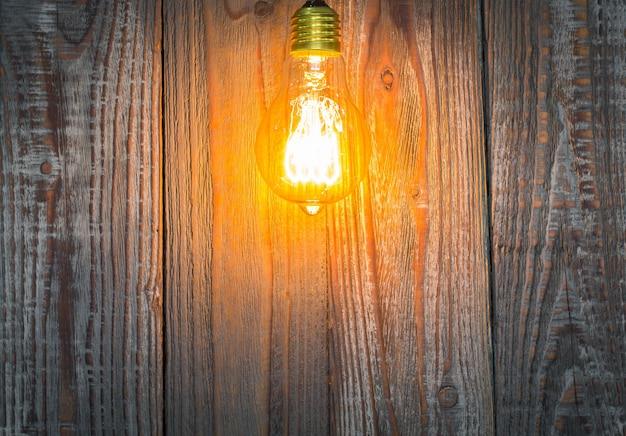Деревянный фон с освещенной лампочкой