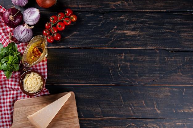 피자 재료와 나무 배경입니다. 빨간색 체크 무늬 냅킨이 있는 회색 나무. 공간을 복사합니다. 평면도