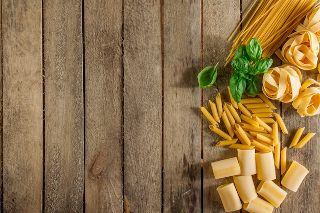 Wooden background with italian pasta and basil