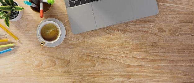 Деревянный фон с клавиатурой ноутбука, канцелярские принадлежности для кофе, небольшое растение в горшке и копией пространства