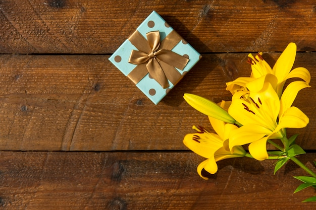 Wooden background with lilies and cute gift