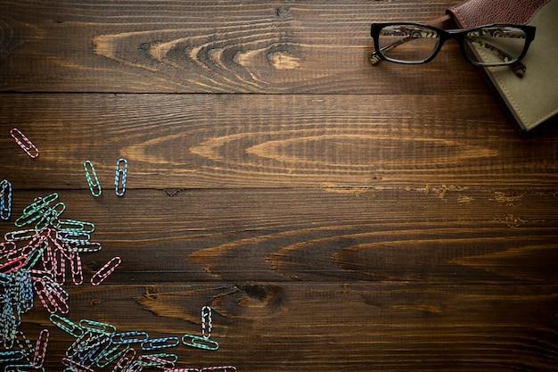 Деревянный фон с тетрадью и красочными скрепками. место для текста