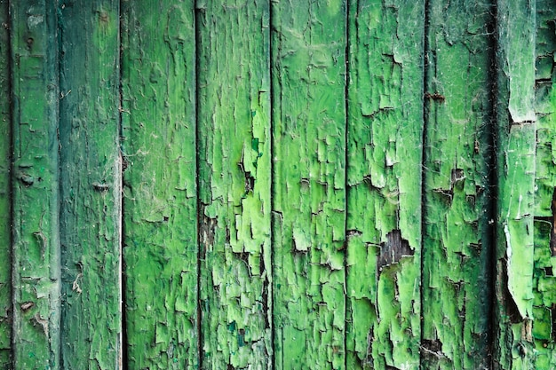 Wooden background with peeling green paint