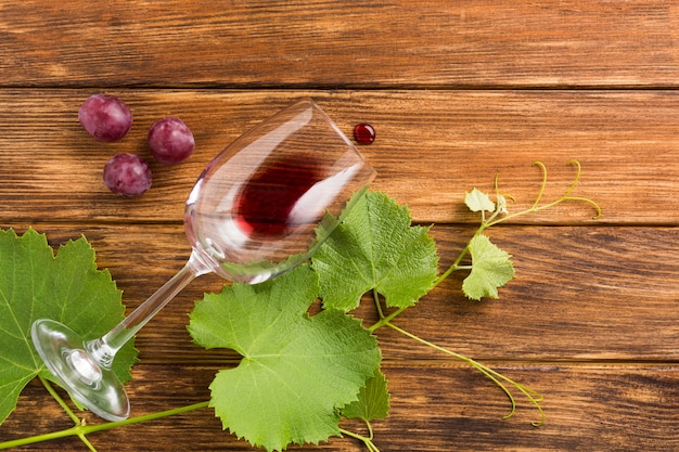 Wooden background with red grapes and vines