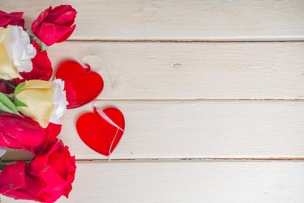 バラとハートの木製の背景。バレンタインデー、誕生日、女性の春の休日の背景、母の日のコンセプト。テキスト用のコピースペースを備えたフラットレイ上面図