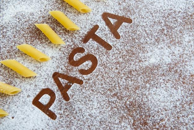 Деревянный фон с посыпанной мукой и написанным словом макароны