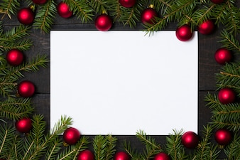 Wooden background with white card and Christmas decoration