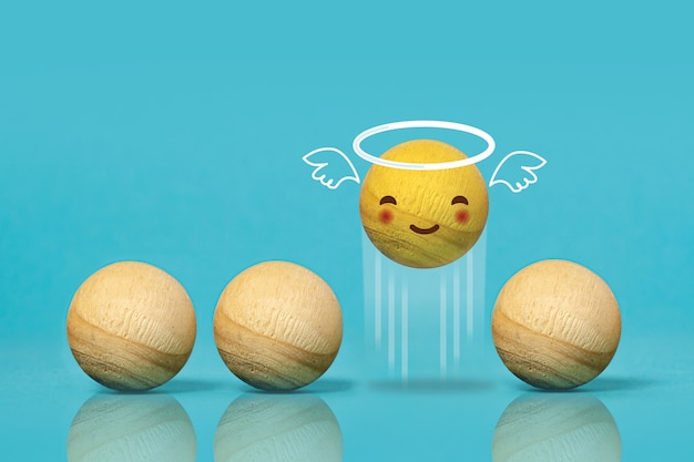 Wooden balls as angel emoticon on blue background