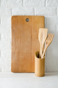 Wooden or bamboo cutlery and cutting board in interior of white kitchen.