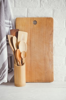 Wooden or bamboo cutlery, towel and cutting board in interior of white kitchen.