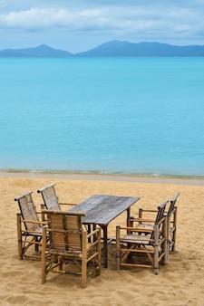 모래 해변에 있는 나무 대나무 가구 테이블과 의자 5개