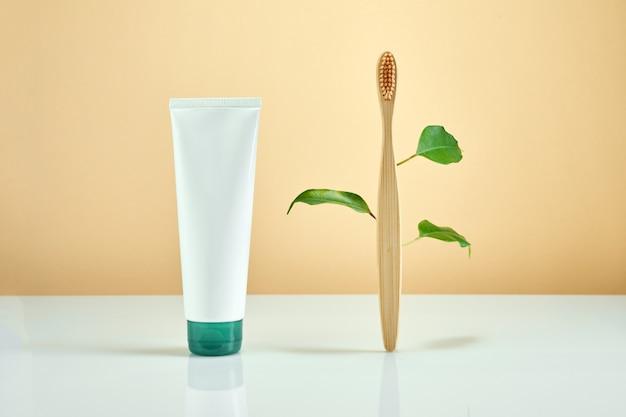 パステルカラーの背景に葉と歯磨き粉と木製の竹の歯ブラシ。ゼロウェイストと環境にやさしいコンセプト。