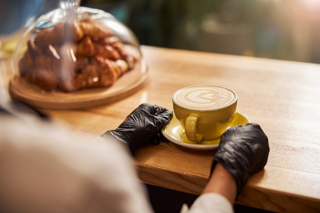 Wooden bar counter with a cup of coffee on a plate. hands in black rubber gloves touching it