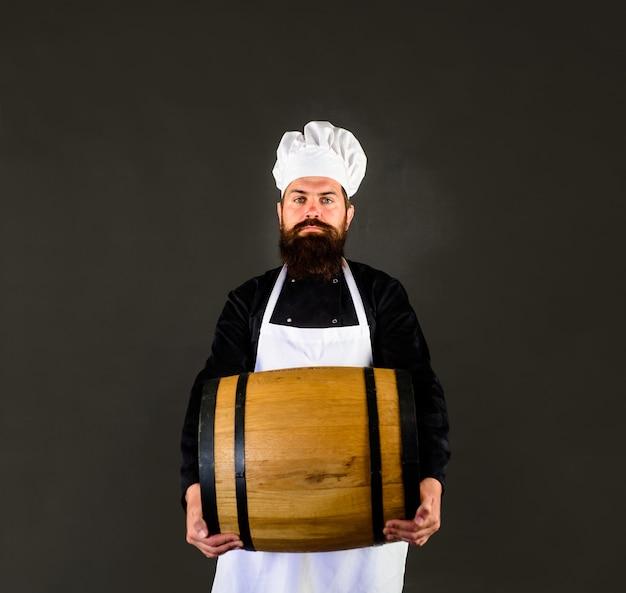 Wooden barrel of beer beer in germany bearded cook with wooden barrel of beer barman equipment for