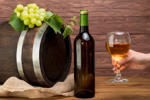 Botte di legno con bottiglia e bicchiere di vino