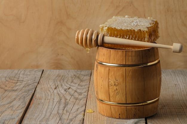 蜂蜜の入った木製の樽、木のスプーンの入ったハニカム、テーブルの上に落とします。セレクティブフォーカス。
