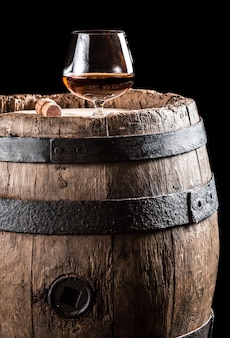 Wooden barrel with wine on wood surface
