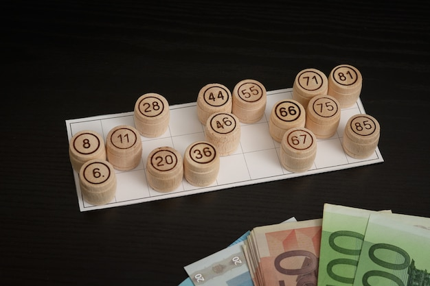Wooden barrels lotto, cards and euro. black wooden table.