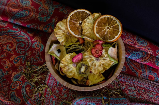Wooden basket filled with dried fruits top view