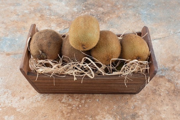 A wooden basket of fresh kiwi on marble table.