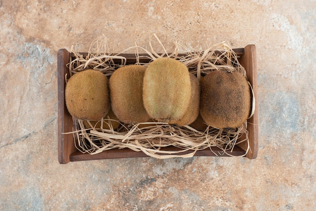 A wooden basket of fresh kiwi on marble