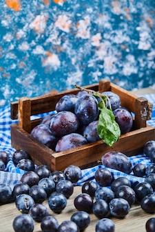 Cestino di legno delle prugne fresche sull'azzurro.