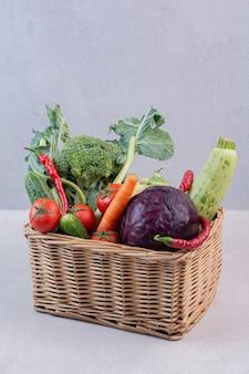 Wooden basket of fresh vegetables on white surface