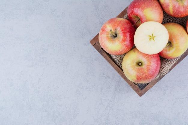 Un cesto di legno pieno di mele su sfondo bianco. foto di alta qualità