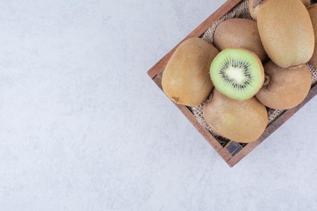 Un cesto di legno pieno di kiwi freschi su sfondo bianco. foto di alta qualità