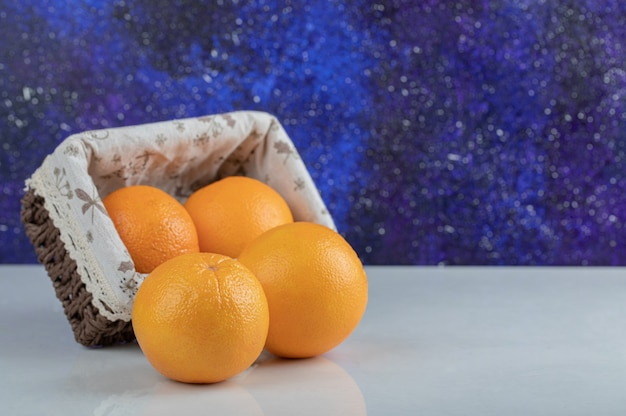 Un cesto di legno pieno di frutta fresca d'arancia.