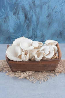 Wooden basket full of oyster mushroom on sack.