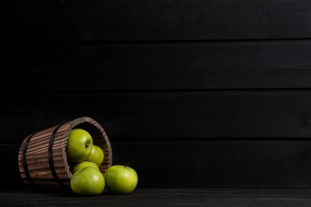 A wooden basket full of ripe green apples placed on a dark wooden table . high quality photo
