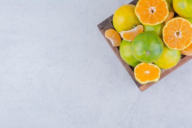 Un cesto di legno pieno di mandarini a fette su sfondo bianco. foto di alta qualità