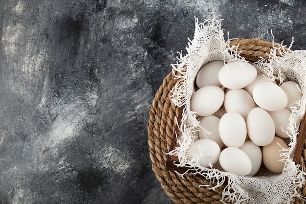 A wooden basket full of white raw chicken eggs .