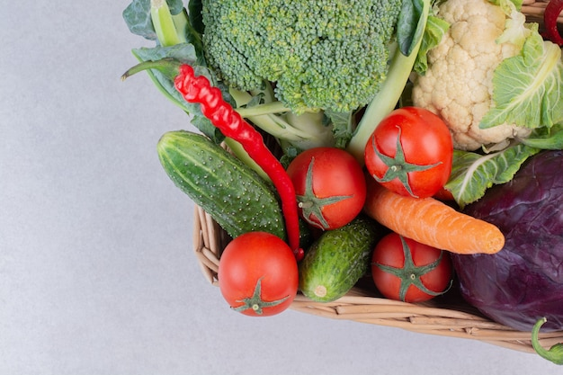 白い表面に新鮮な野菜の木製バスケット