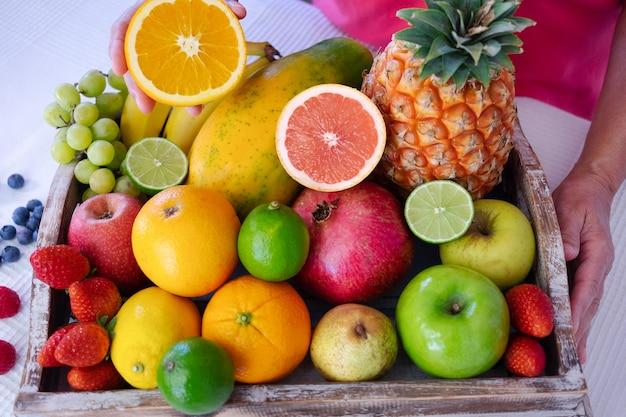 新鮮なカラフルな果物でいっぱいの白いテーブルの上の木製のバスケット。オレンジ色の果物の半分を保持している成熟した女性。健康的な食事とライフスタイル