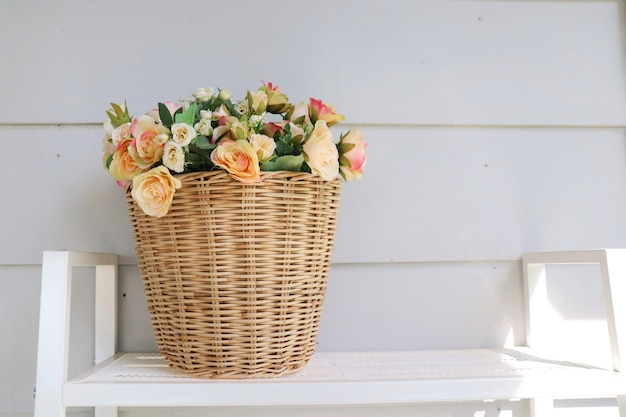 A wooden basket pot of bouquet pink and orange flowers on the wooden table with white wall.