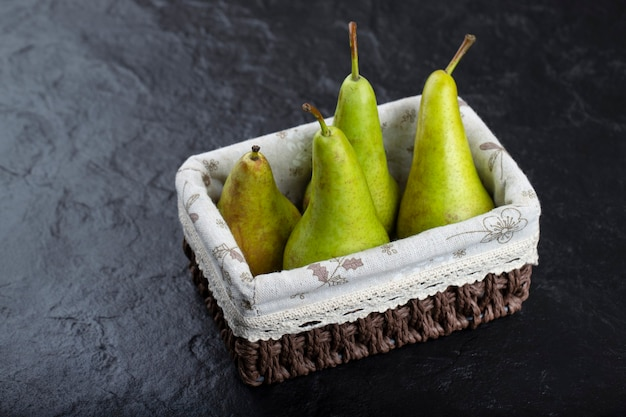 Wooden basket of ripe green pears on black background.