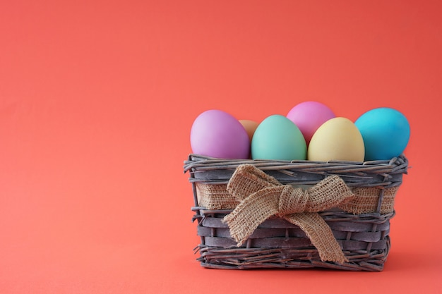 Wooden basket with beautiful colorful eggs happy easter,  good blank for a greeting card.