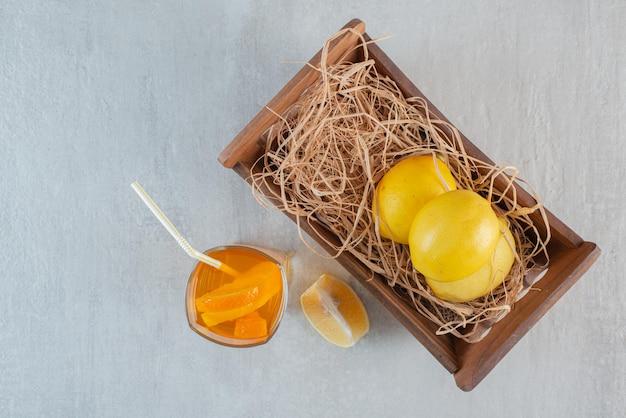 Un cesto di legno con limoni e un bicchiere di succo
