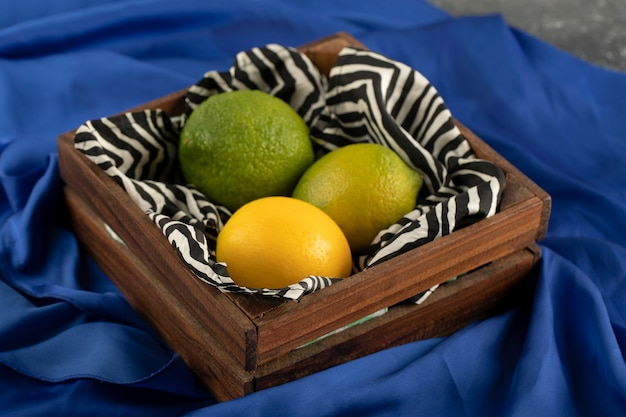 A wooden basket with three lemons on a blue cloth.