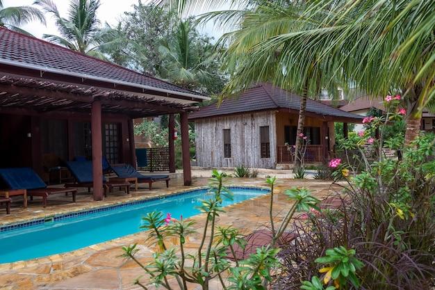 Деревянное бунгало на пляже с бассейном и фоном кокосовой пальмы. африка, танзания, занзибар, кендва. концепция летних каникул.
