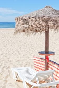 Деревянный пляжный зонтик и шезлонг на пляже. к праздникам.
