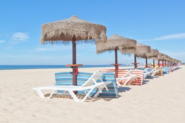Деревянные пляжные зонтики и шезлонги на пляже. к праздникам.