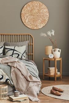 デザイン家具、装飾、カーペット、本、花瓶のドライフラワー、ベッドシーツ、毛布、枕、家の装飾のエレガントなパーソナルアクセサリーを備えたスタイリッシュなニュートラルなベッドルームのインテリアの木製ベッド