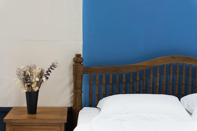 ベージュのカーテンの背景が付いている寝室でモダンに装飾された木製のベッドのサイドテーブル