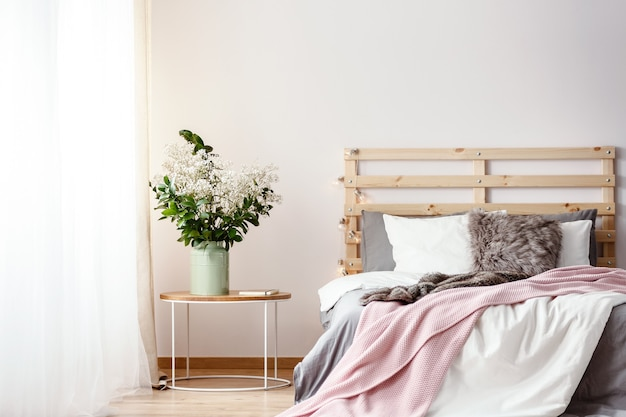新鮮な植物やドレープのある明るい部屋のインテリアに立っている毛皮の枕、灰色のシーツ、ピンクの毛布付きのダブルベッドのそばにライトが付いた木製のベッドヘッド